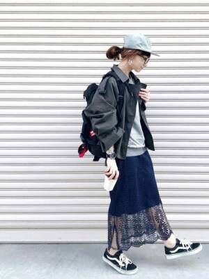 黒いジャケットにレーススカートを合わせて黒いスニーカーを履いた女性