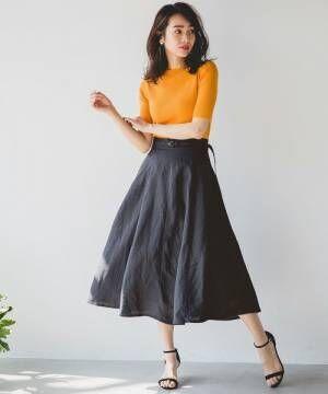 オレンジトップスにネイビーのリネンスカートを履いた女性