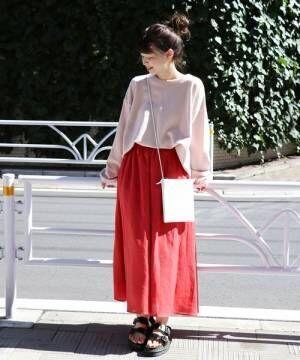 ピンクのトップスにピンクのスカートを合わせて白いバッグを持った女性