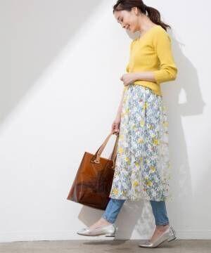 黄色いトップスに花柄のスカートを合わせてシルバーの靴を履いた女性