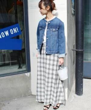 デニムジャケットにチェックのスカートを合わせて白いバッグを持った女性