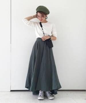 白いトップスにカーキのスカートをあわせて黒いバッグを持った女性
