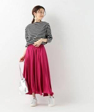 ボーダートップスにピンクのスカートを合わせて白いスニーカーを履いた女性