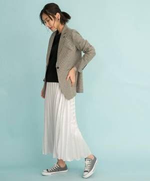 黒いトップスに白いスカートを合わせてチェックのジャケットを羽織った女性