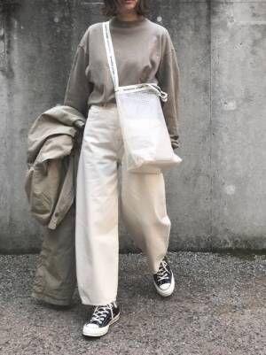 グレージュのトップスに白いワイドパンツを合わせて黒いスニーカーを履いた女性