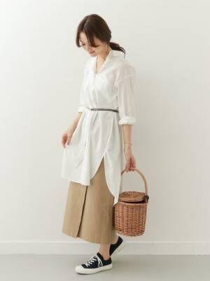 白いロングシャツにチノスカートを合わせてかごバッグを持った女性
