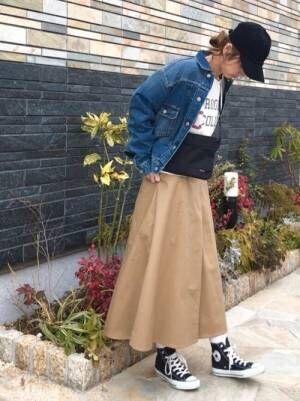 ロゴトップスにチノスカートを合わせてデニムジャケットを羽織った女性