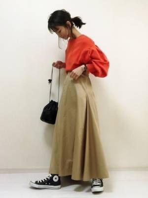 赤いスウェットトップスにチノスカートを合わせて黒いバッグを持った女性