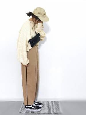 白ニットにラインパンツを履いた女性