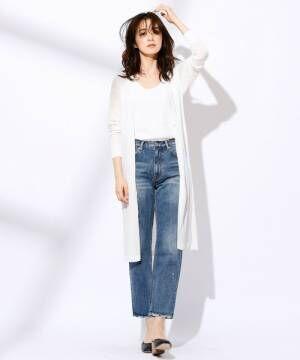 白のトップス、デニムパンツに白のロングカーディガンを着た女性
