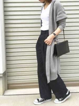 白のトップス、ネイビーのワイドパンツにグレーのロングカーディガンを着た女性