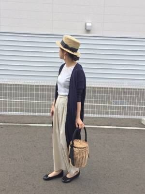 白のトップス、ベージュのパンツにネイビーのロングカーディガンを着た女性