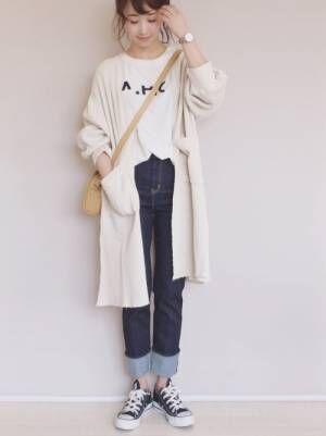 白のロゴT、デニムパンツに白のロングカーディガンを着た女性