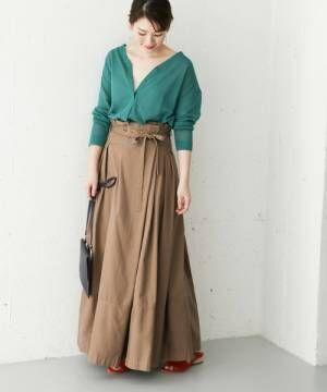 グリーンのカーディガンにベージュのラップフレアスカートを履いた女性