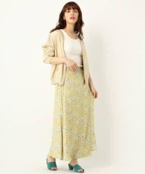白のタンクトップ、黄色の花柄ラップスカートにベージュのカーディガンを着た女性