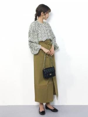 モノトーンの花柄ブラウスにベージュのラップスカートを履いた女性