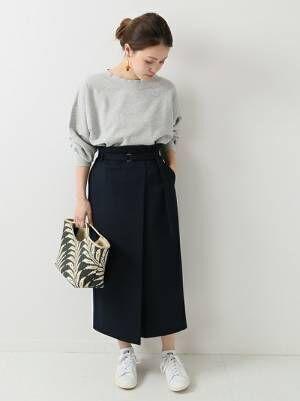 グレーのスウェットにネイビーのラップスカートを履いた女性