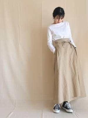 白のカットソーにベージュのラップマキシスカートを履いた女性