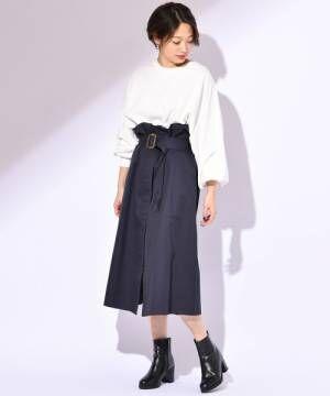 白のトップスにネイビーのラップスカートを履いた女性