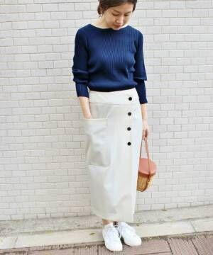 ネイビートップスに白いラップスカートを履いた女性