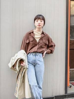 ベージュのハイネックリブニットにブラウンシャツ、デニムパンツを履いた女性
