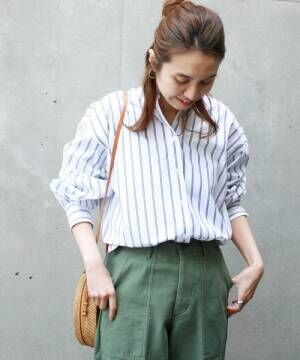 ストライプシャツにカーキパンツを履いた女性