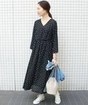 黒のドット柄ワンピースを着た女性