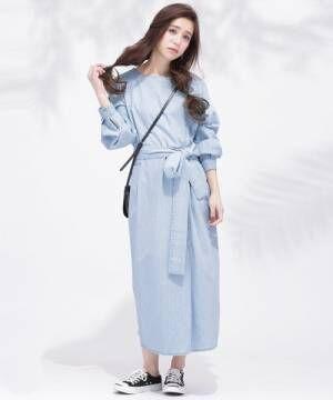 サックスブルーのデニムワンピースを着た女性