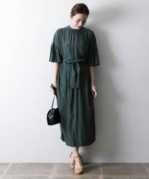 グリーンのクルーネックワンピースを着た女性