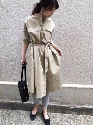 ベージュのシャツワンピにグレーのレギンスを履いた女性
