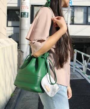 グリーンの巾着型ショルダーバッグを掛けた女性