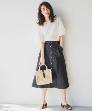 白トップスにデニムAラインスカートを履いた女性