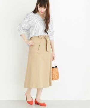 ストライプ柄ブラウスにベージュスカートを履いた女性