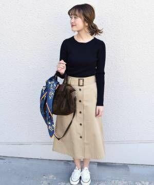 黒のトップスにベージュのスカートを履いた女性