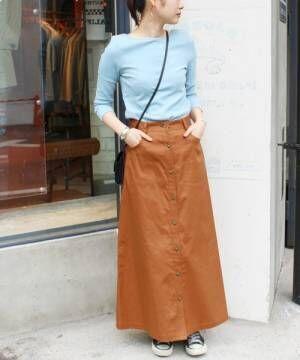 ライトブルーのリブトップスにキャメルのスカートを履いた女性
