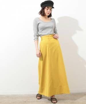 グレーのトップスに黄色のスカートを履いた女性