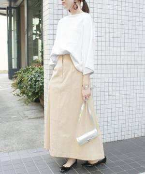 白のカットソーにベージュのスカートを履いた女性