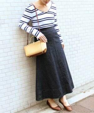 ボーダートップスにデニムロングスカートを履いた女性