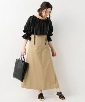 黒のブラウスにベージュのサス付きスカートを履いた女性