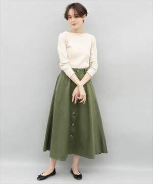 ベージュのリブトップスにカーキのスカートを履いた女性