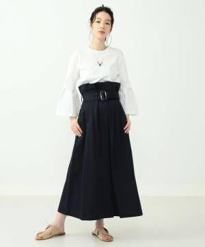 白のブラウスにネイビーのスカートを履いた女性