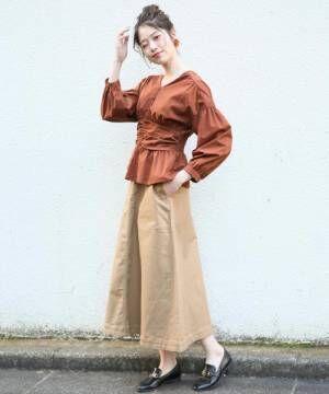 ブラウンのブラウスにベージュのスカートを履いた女性