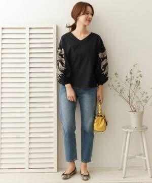 黒い刺繍ブラウスにデニムパンツを履いた女性