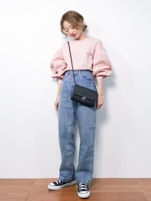 ピンクのブラウスにワイドデニムパンツを合わせた女性