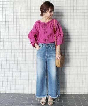 ピンクの刺繍ブラウスにデニムパンツを合わせた女性
