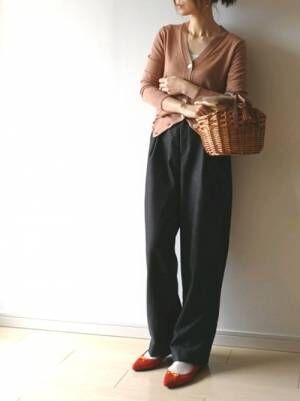 ピンクベージュのカーディガンに黒のワイドパンツ、かごバッグを合わせたコーデ