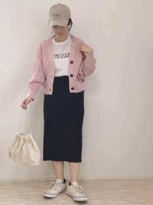ロゴTシャツに黒のタイトスカート、ピンクのカーディガンを羽織り、キャップを合わせたコーデ