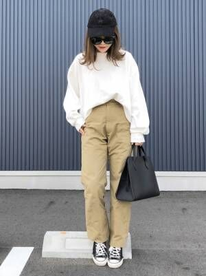 白のトップスにベージュのチノパンを履いた女性