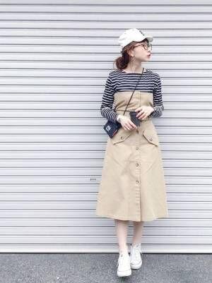 ボーダートップスにベージュのビスチェ付きトレンチスカートを履いた女性