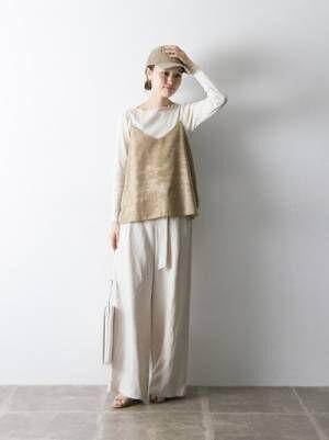 白のリブトップス、ワイドパンツにベージュのキャミソールを着た女性